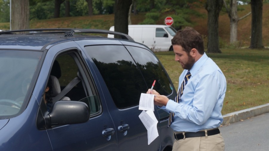 """Pictured above is new parking lot supervisor Dana Kanupp checking the name of a leaving student.  Kanupp has been hired to regulate students leaving campus. """"My main responsibility is to keep everybody safe, which entails students not doing what they're not supposed to be doing,"""" Kanupp said."""