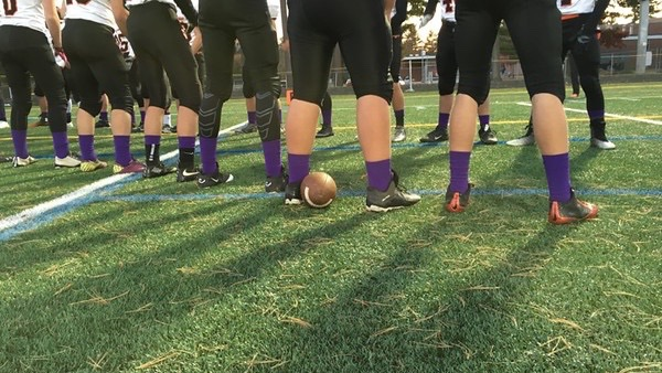 Pictured above is the Wayland football team warming up for their game against Bedford. The team is wearing purple socks during the month of October to raise awareness for domestic violence.