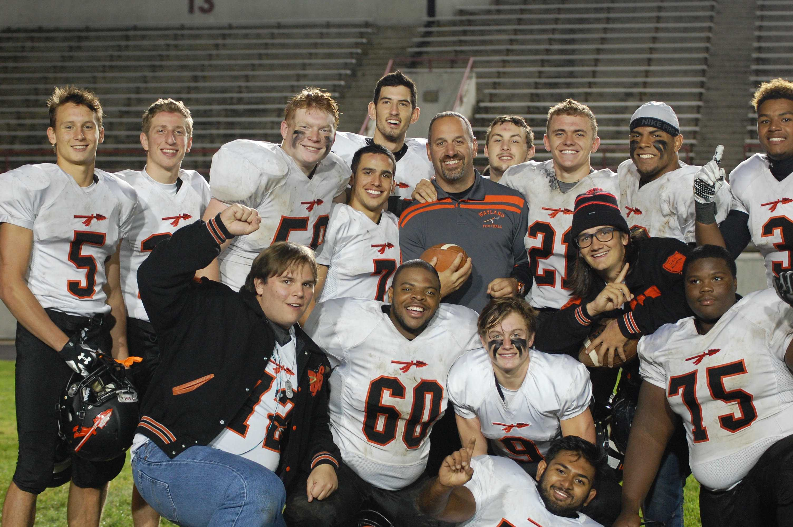Pictured above is head coach Scott Parseghian with his players. The Warriors' win against Boston Latin on Friday marked Parseghian's 100th win at Wayland.