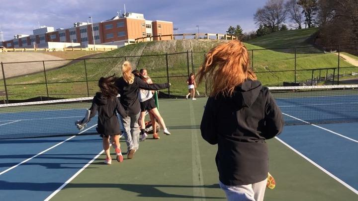 Pictured+above+is+the+girls%27+tennis+team+celebrating+after+their+win+over+Concord-Carlisle.+%E2%80%9CI+think+%5Bbeating+CC%5D+showed+the+girls+that+we+can+really+make+some+noise+in+the+state+tournament+if+we+keep+working+hard%2C%E2%80%9D+coach+Erin+Reeves+said.