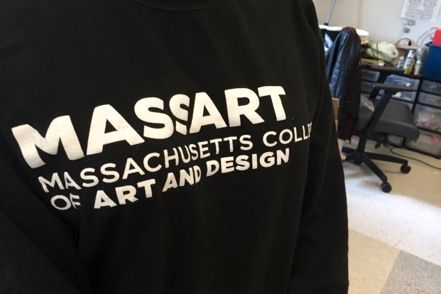 """Pictured above is senior Olivia Stitham wearing a Massachusetts College of Art and Design shirt. Stitham was one of the six Wayland High School students who applied to art school this year. """"The process is really fun, but also exhausting. You get to make a ton of art, but you have to photograph, edit, mat, upload and submit all of your work, which takes more than a period I learned,"""" Stitham said."""