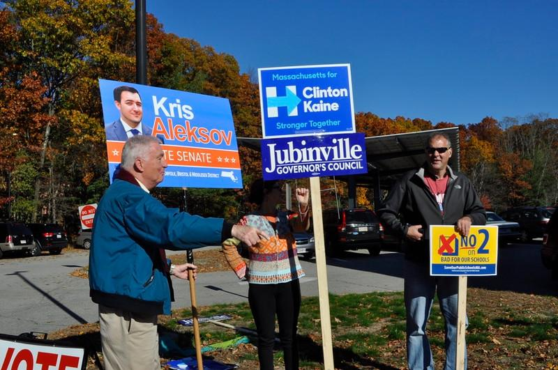 """Above, Wayland residents Rodney Hager, Martha Locke and Anthony Dias hold political signs outside Wayland Middle School. Wayland voters cast their ballots in the U.S. presidential election on Tuesday. Every vote counts. All it takes is one,"""" Psiaf said."""