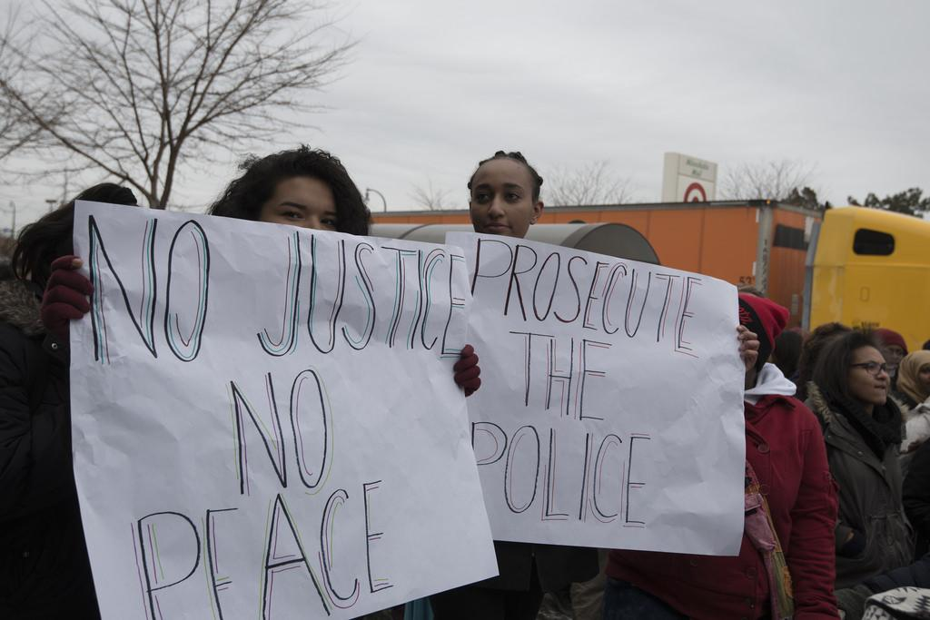 Pictured above are demonstrators holding signs. Guest writer Yaniv Goren argues that more teenagers would be involved in politics if the pressures of high school didn't get in the way.