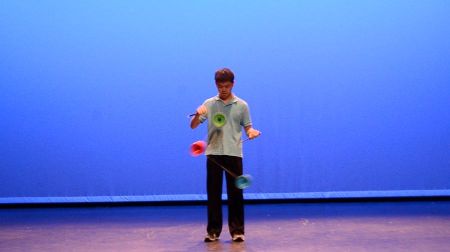 Wang performs a triple yo-yo trick, spinning three yo-yos around and into the air on a string.