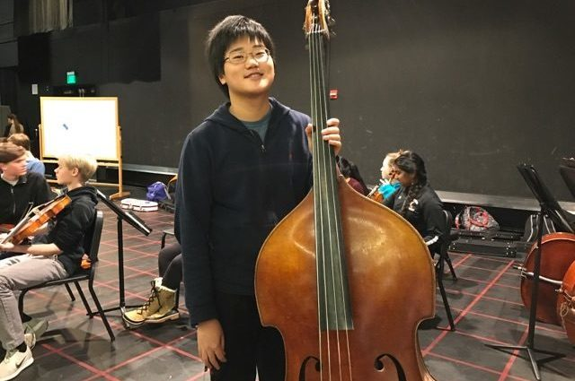 "Above is freshman Jesse Wang with his bass. Wang will play in the All-State music festival this year, having put in years of practice to excel on bass. ""#NeverGiveUp. Work hard at something that you want and be dedicated."" Wang said."