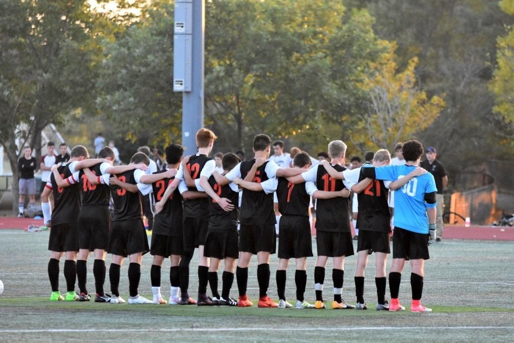 The boys' soccer team stands in memory of Cameron Tredgett at their game on Saturday night.