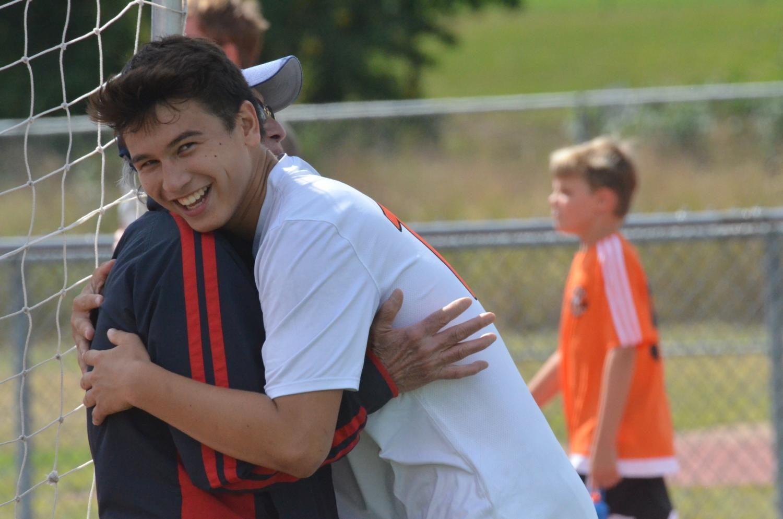 Junior Jake Tyska hugs his grandfather after defeating Snowden International 8-0.