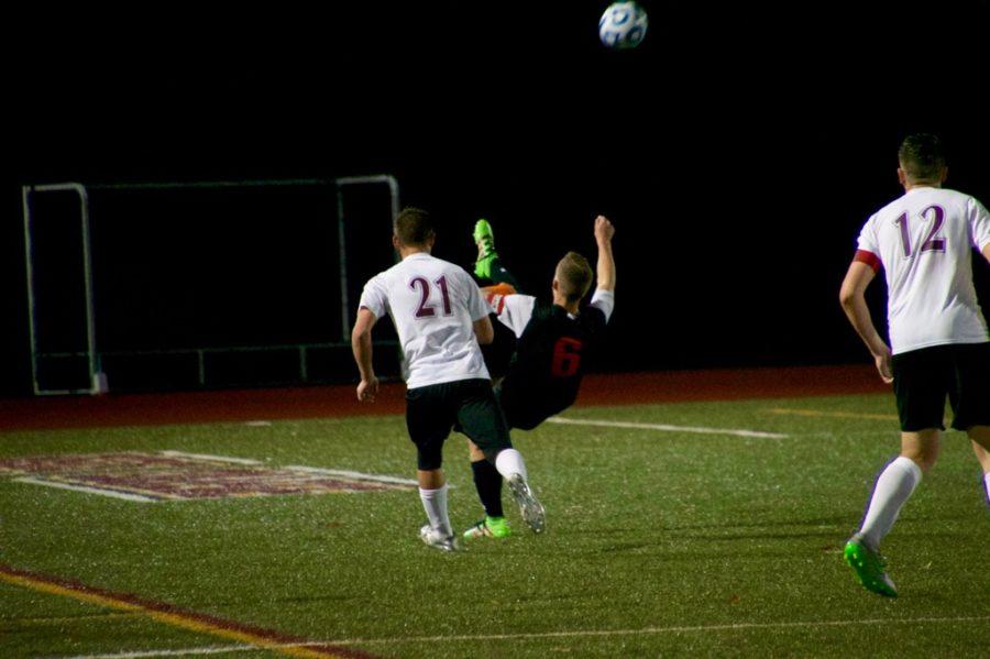 Senior+captain+Zack+Dresens+kicks+the+ball+over+his+head.