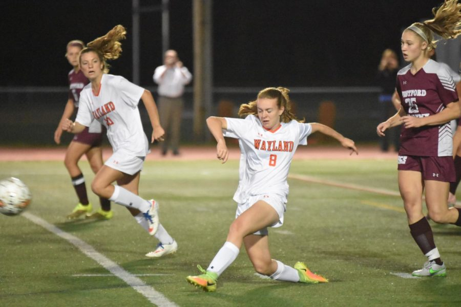 Sophomore Kayla Poulsen falls as she kicks the ball out of the defensive end.