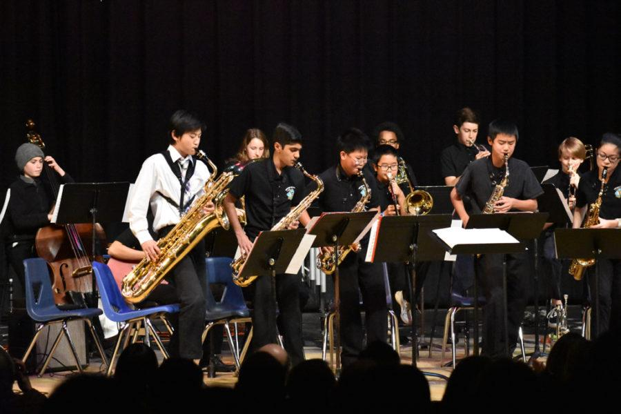 Baritone saxophonist Brasen Chi, tenor saxophonists Ayaan Rashid and Isabelle Wang, and alto saxophonists Eric Xie and Andrew Zhao lean in toward their music stands as they solo in