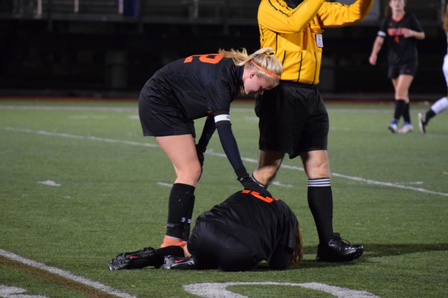 Mabe talks to junior Eden Vanslette after she is hurt on the field.
