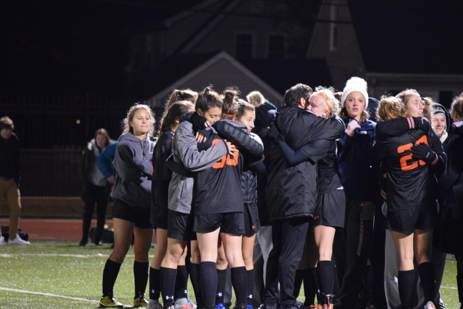 Members of the girls' varsity soccer team comfort each other after their loss.
