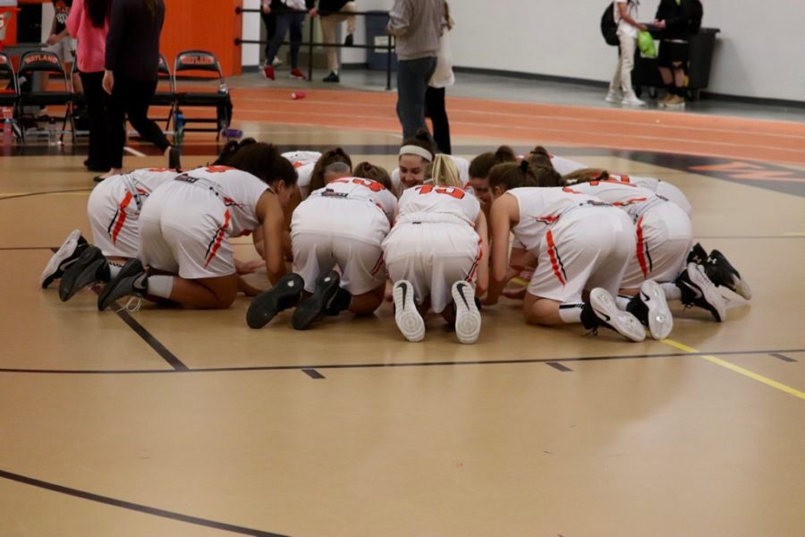 The+girls%27+varsity+basketball+team+huddles+together+before+the+game.