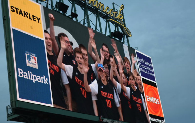 Pictured above is the WHS boys' varsity soccer team projected on the Fenway Park jumbotron after winning a state championship. Colin Meiselman is second from the left.