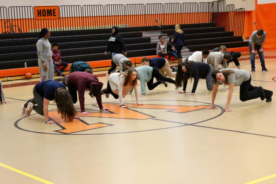 Freshman girls work out their abs with some mountain climbers.