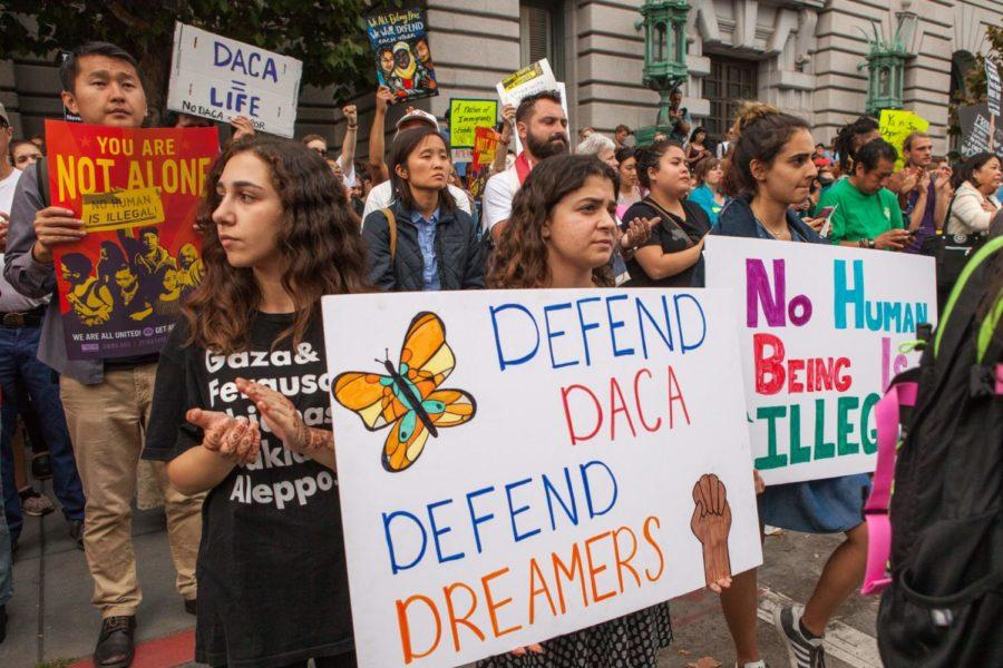 People hold up signs for DACA.