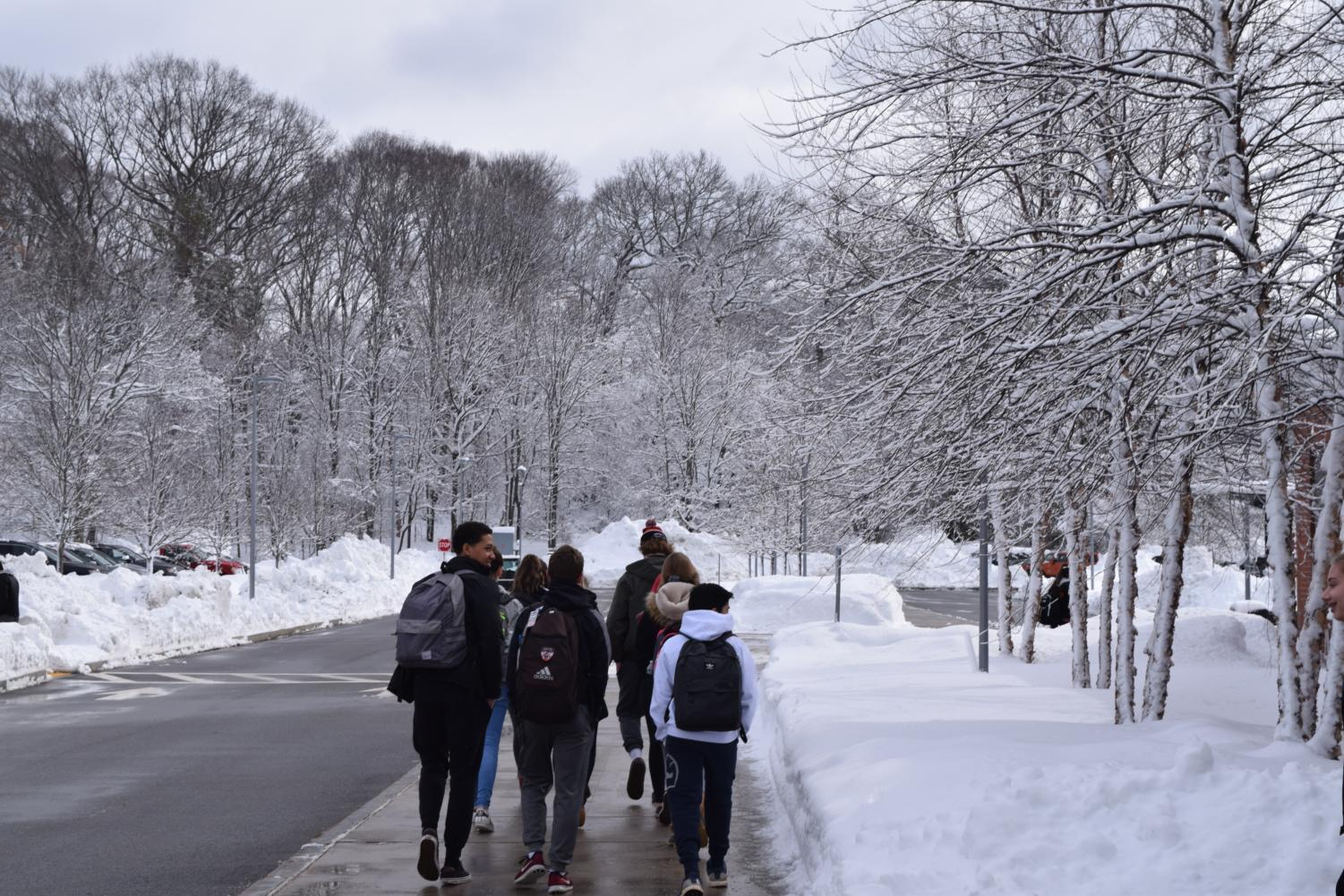 Students walk in the snow. WPS Superintendent recently announced a two-hour delay to school start times tomorrow, with the potential for a full cancellation by 5:15 a.m. on Tuesday morning.