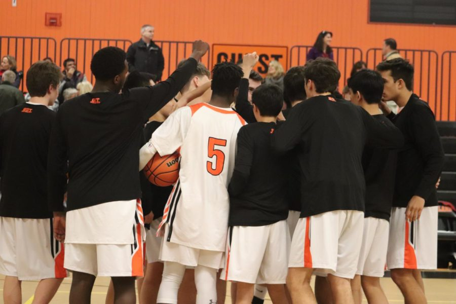 The+boys%E2%80%99+varsity+basketball+team+huddles+before+facing+Westborough.+