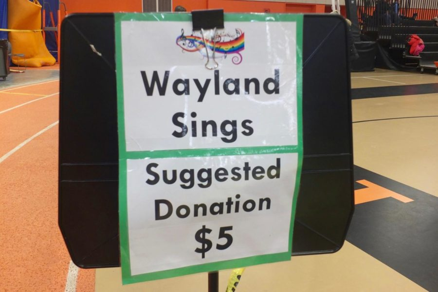 A Wayland Sings donation sign is posted at the entry of the concert.