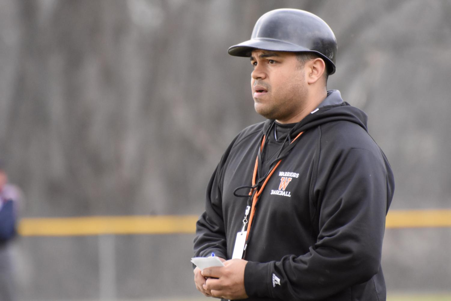Paul Bonfiglio, the new head baseball coach at Wayland High School, looks down the line and gives signals to his team.