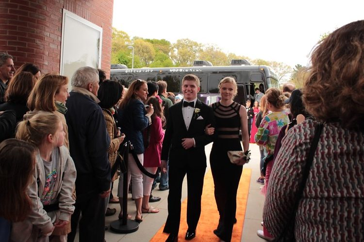 Seniors+Ian+Reilly+and+Kayla+Mabe+walk+down+the+orange+carpet+at+prom.++