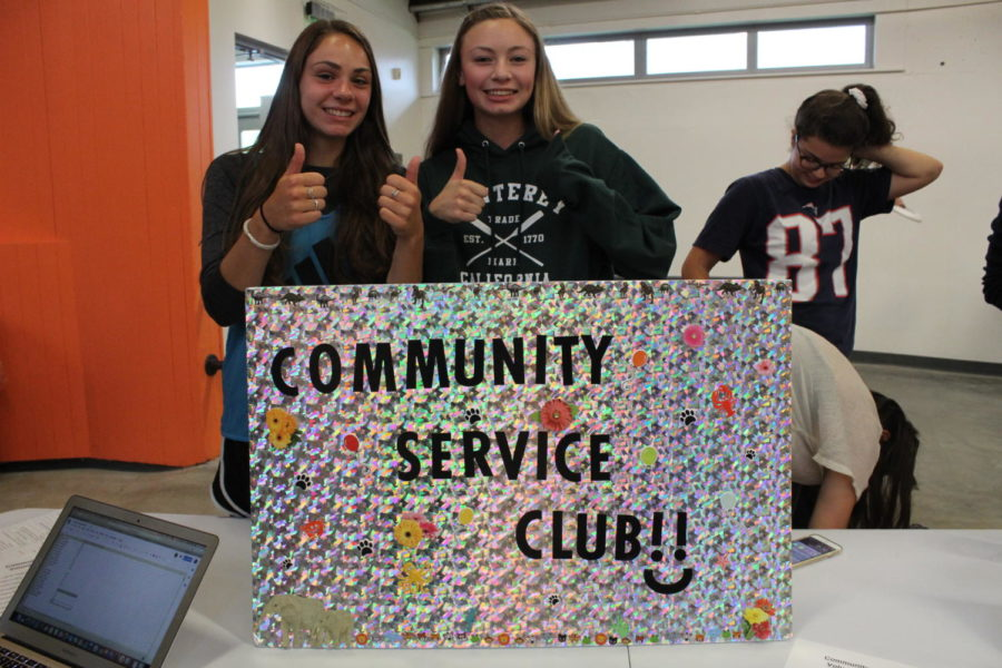 Juniors Jenna Ferrick and Savannah Sugar smile at the community service club table.