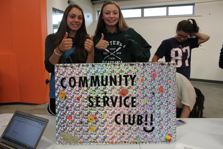 Juniors Jenna Ferrick and Savannah Sugar smile at the community service club table.
