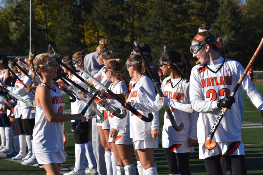 The girls' varsity field hockey team slaps sticks at the beginning of their game against Waltham.  The team fell to Waltham on October 18.