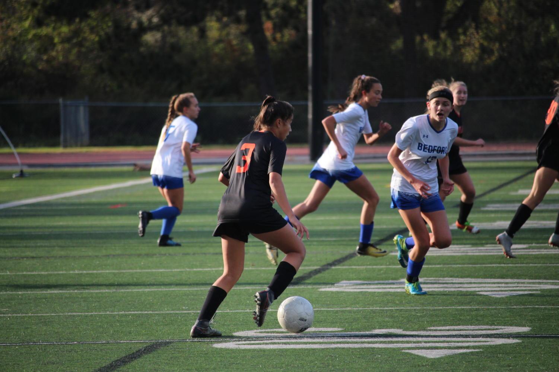 Sophomore+Ellie+Tyska+dribbles+towards+the+offensive+zone.