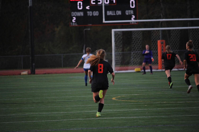 Junior+captain+Kayla+Poulsen+runs+down+the+field+to+follow+the+play.