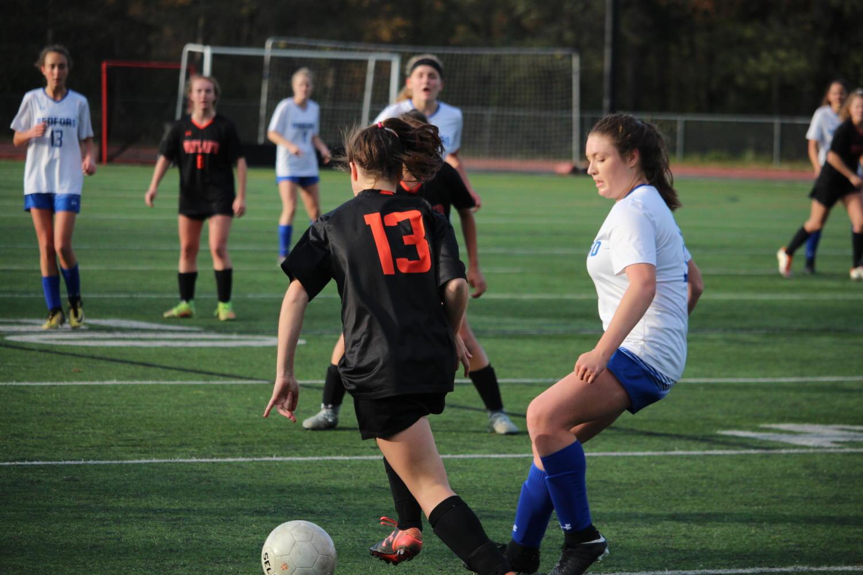 Senior+Abby+Obar+dribbles+the+ball+past+Bedford+defense.