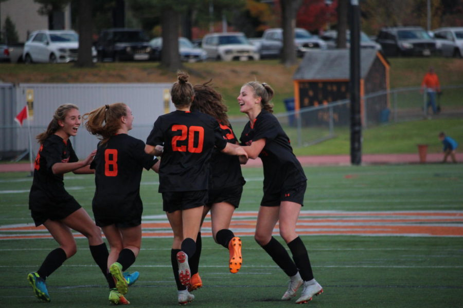 Girls' soccer celebrates after the first goal of their 3-0 game against Bedford.  This win on Oct. 23 put girls' soccer into first place in the DCL Small.