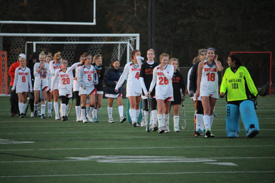 The girls' varsity field hockey team walks off the field after falling 0-5 to Natick in its last home game of the season.