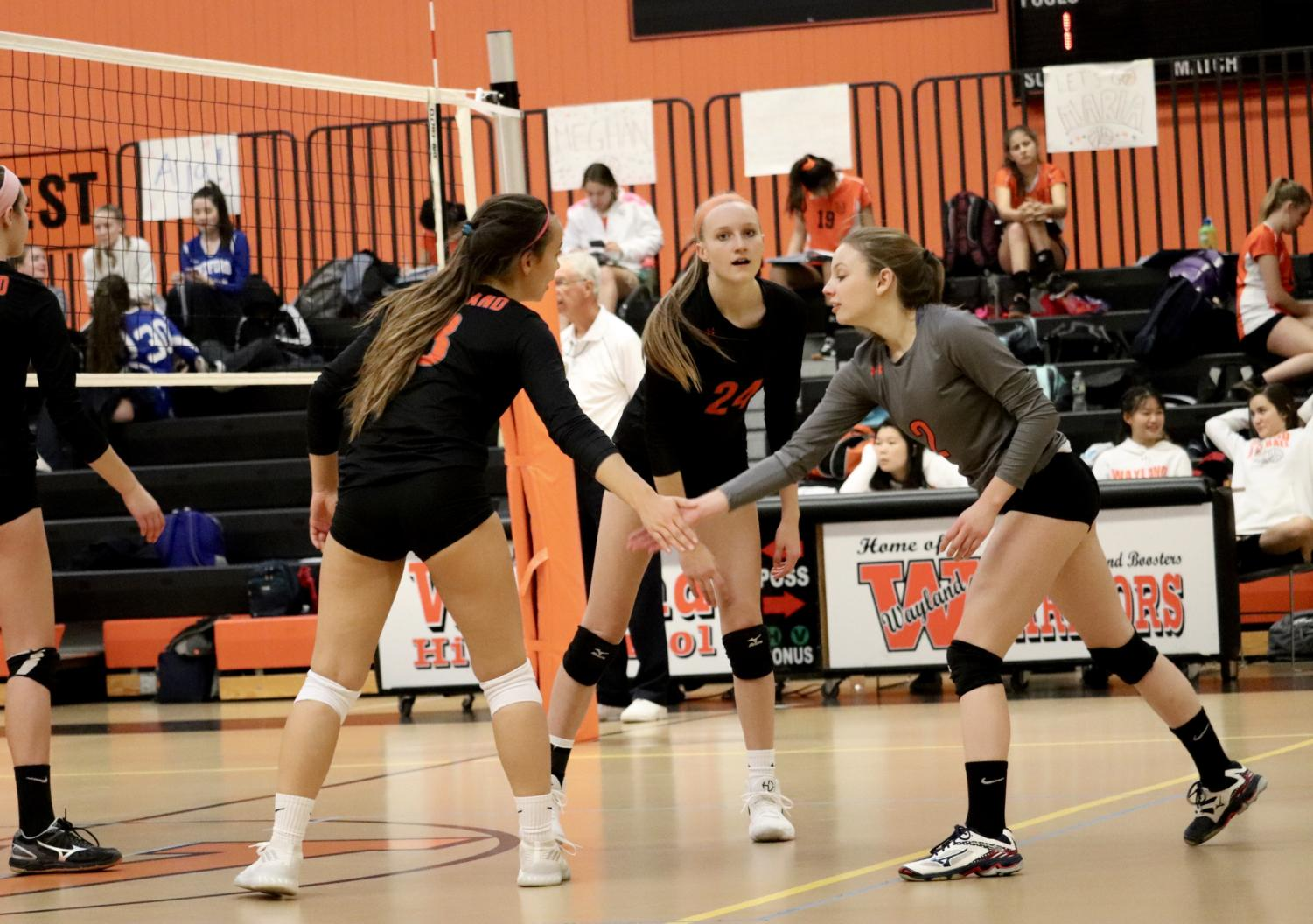 Captains+junior+Ava+Tang+and+senior+Noelle+McGah+high-five+junior+Izzy+VanRooyen+during+a+game+against+Bedford.+The+No.+19-seeded+girls%27+volleyball+team+defeated+No.+2+Danvers+in+the+first+round+of+playoffs.+%E2%80%9COver+time%2C+the+volleyball+program+has+been+getting+stronger%2C%E2%80%9D+Tang+said.+%0A