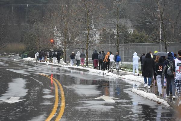 Students+walk+past+the+softball+field+in+the+rain.