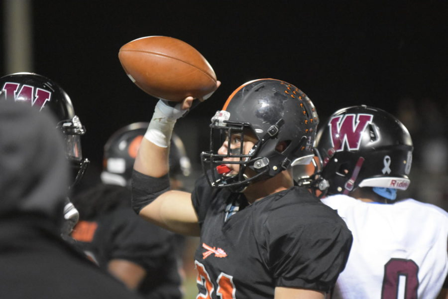 Senior Wellington Pereira holds up a ball on the sidelines.