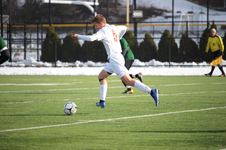Freshman+Jackson+Dresens+dribbles+the+ball+up+the+field.