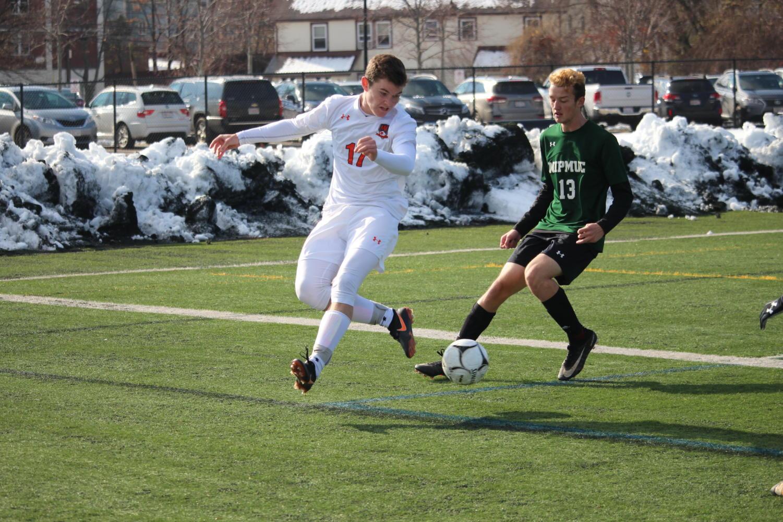 Senior+Jack+Dretler+passes+the+ball+back+up+the+field.
