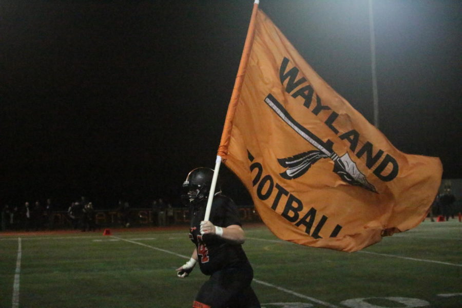 Junior Phillip Koechling carries out the Wayland flag as the Warriors run out to the field after halftime. Wayland defeated Dracut 34-26 in 2OT on Friday.
