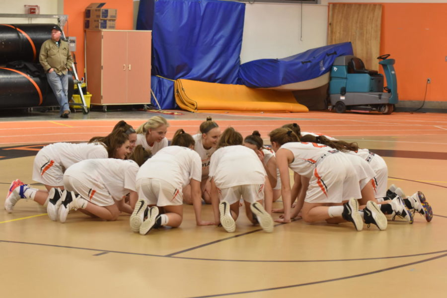 The team huddles for their pre-game pep talk. Their ritual before games is to crouch, bang their hands on the floor and do a Wayland cheer.