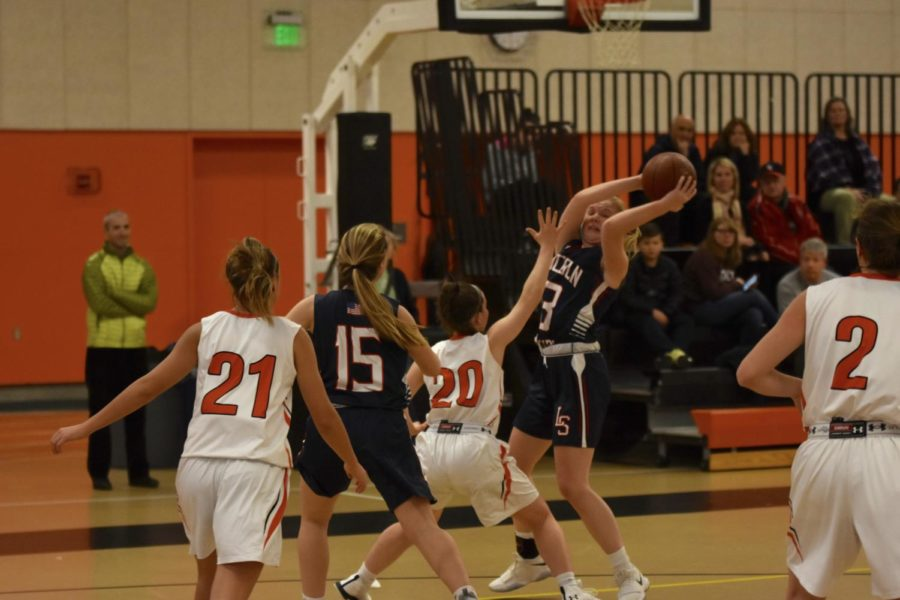 Balicki sticks her hand up in an attempt to break the LS offensive play. LS senior Paige Maxwell bends back to try and fake Balicki out.