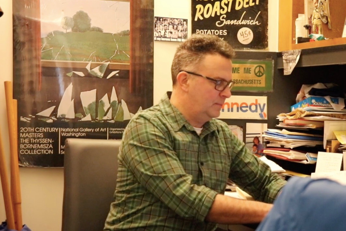"""History department head Kevin Delaney prepares for class at his desk. Delaney's upbringing largely contributed to his passion for history. """"I've always liked working with young people,"""" Delaney said."""