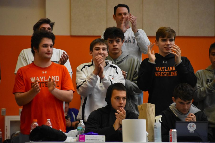 Wayland wrestling team members cheer as Morris receives two back points from his turn on his opponent. They watch intently as Morris fights to win the match.