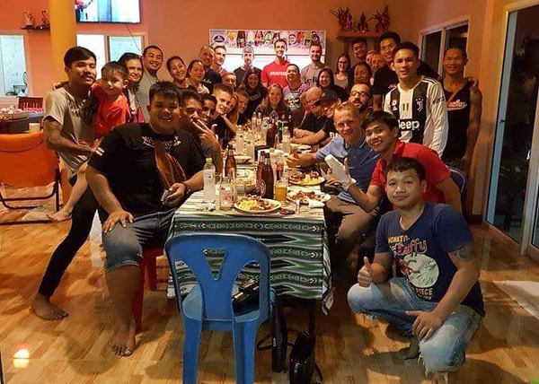 """2018 graduate Peter Wolff shares a meal with Thai students. While staying in Thailand, Wolff was able to focus on his studies of Muay Thai. """"I was staying in the middle of nowhere,"""" Wolff said. """"There were rice fields all around, and the fun thing to do was to go to 7/11 and get a snack. It [was] good because there [were] not many distractions."""""""