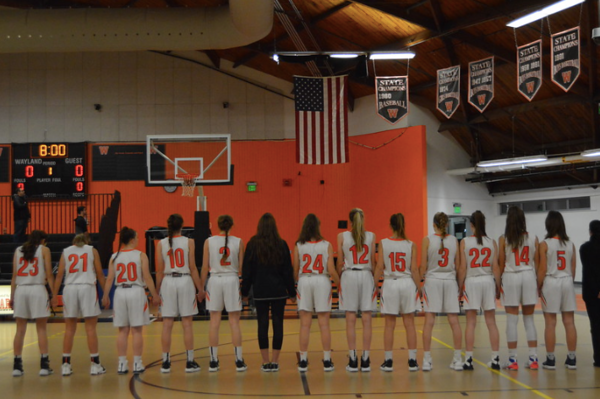 The girls varsity basketball team holds hands for the National Anthem before their game against Boston Latin on December 14. The girls' use of practice players helped them to get a spot in the playoffs.