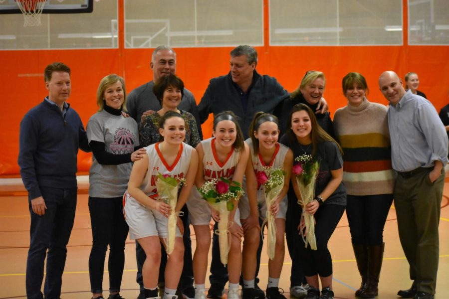 Senior+captain+Kate+Balicki+and+seniors+Lauren+Hanifin%2C+Samantha+Neuman+and+Haley+Rice+pose+with+their+parents+during+the+Senior+Night+ceremonies.+