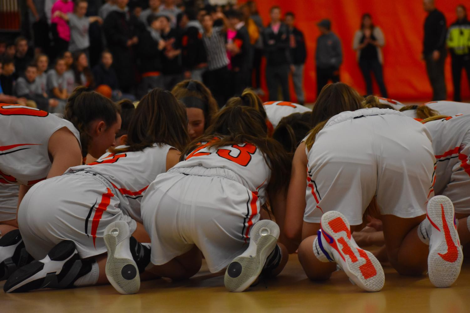 During+their+pre-game+ritual%2C+the+Wayland+girls+get+into+a+tight+huddle+on+the+ground+and+hear+from+captains+Balicki+and+Kiernan.+
