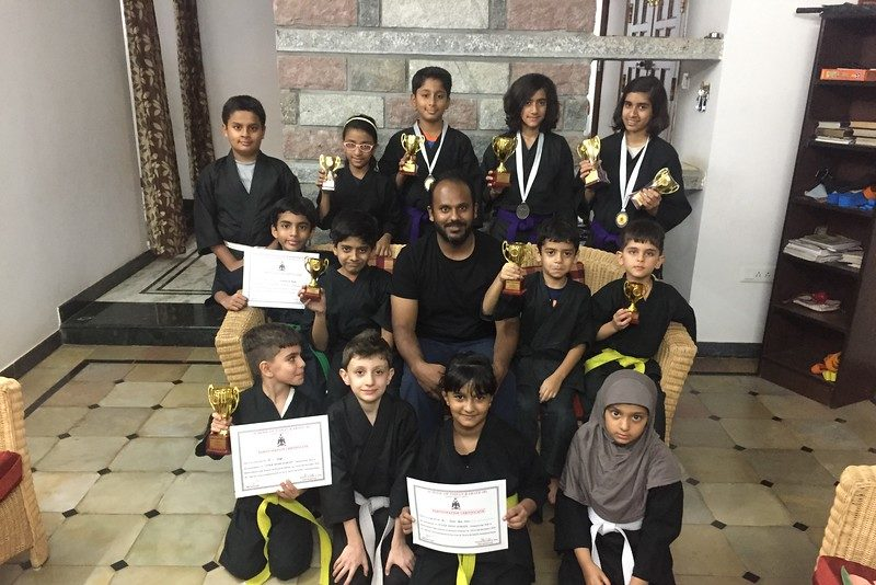 """Freshman Madeeha Syeda (back row, second from right) poses with her karate class, holding her trophy after coming first place in a tournament in 2016. Syeda began karate when she was 7 years old and practiced the martial art for five years before she began mixed martial arts. """"[MMA] gives me one thing that I feel good at,"""" Syeda said. """"It's something that I can feel proud of myself about."""""""