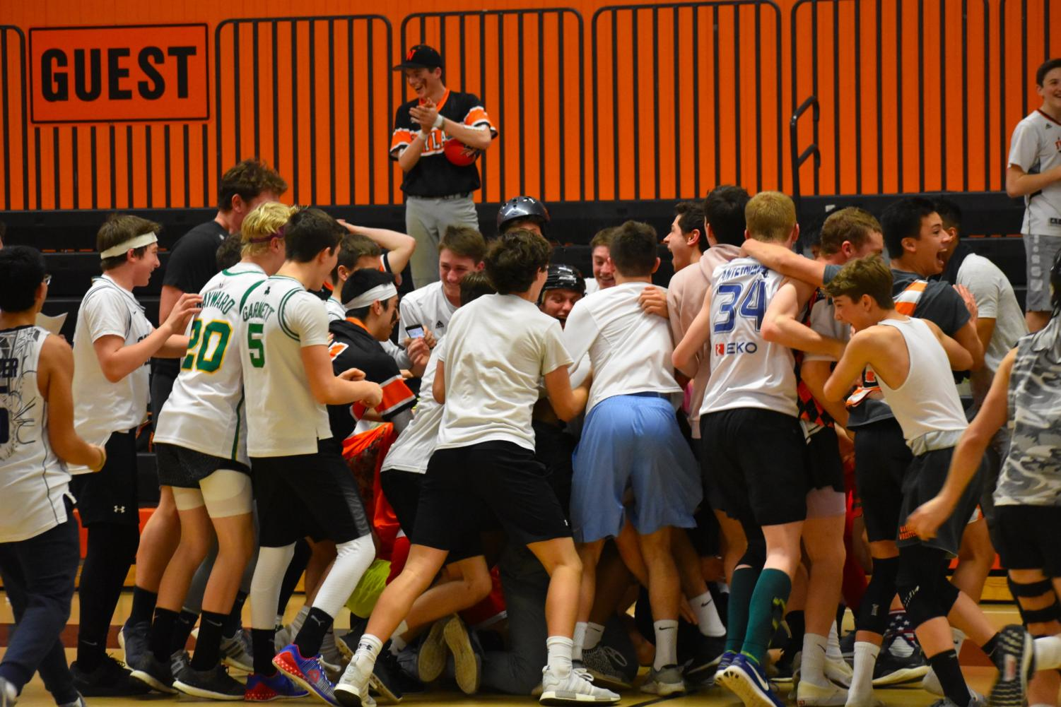 Students run onto the court and form a mosh pit after freshmen team