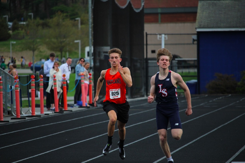 Sophomore+Sean+Keegan+races+an+LS+opponent+during+the+100m+dash.